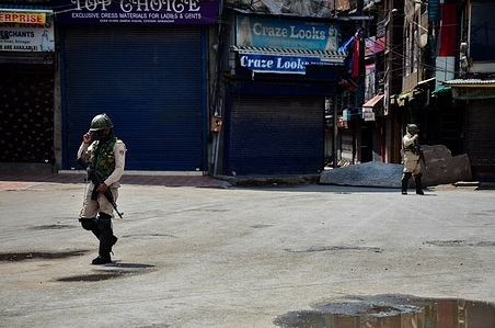 """Paramilitary troopers stand alert at a closed market during strict restrictions imposed on the assassination anniversaries of two prominent separatist leaders Mirwaiz Mohammad Farooq and Abdul Gani Lone, in Srinagar. Strict restrictions were imposed in parts of Kashmir valley on the death anniversaries of Mirwaiz Mohammed Farooq and Abdul Gani Lone. Farooq, the chief cleric in the region's main mosque, was assassinated by unidentified gunmen at his residence on May 21, 1990. Lone was killed in 2002 during a function to mark Farooq's death at Srinagar's """"martyrs graveyard."""""""