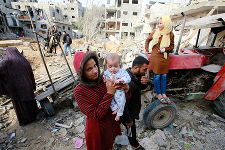 Palestinian family who have returned to their neighborhood, stare at the damages from their home, hit by Israeli bombardment in Gaza City.A ceasefire between Israel and Hamas, the Islamist movement which controls the Gaza strip, appeared to hold today after 11 days of deadly fighting that pounded the Palestinian enclave and forced countless Israelis to seek shelter from rockets.