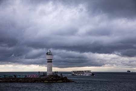 People are seen fishing at the Inciburnu Lighthouse on a cloudy day in Kadikoy district of Istanbul.