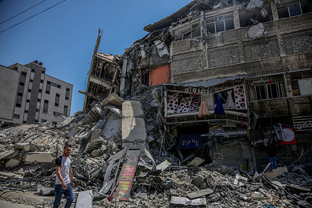 A Palestinian walks past the rubble piled up in Gaza, following the ceasefire agreement between Gaza and Israel. The ceasefire between Gaza and Israel has been implemented.