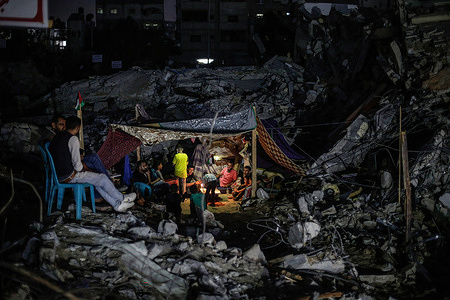 Palestinians seen inside a tent by the rubble of their destroyed house in Beit Hanoun town following the Israel airstrikes in Gaza.Palestinian families started returning to their destroyed houses after 11 days of fighting, a ceasefire came into effect on 21 May between Israel and militants in Gaza strip under an Egyptian initiative for an unconditional ceasefire. At least 232 Palestinians were killed in the Israeli offensive according to Palestinian health ministry, while at least 12 Israelis killed in rocket attacks from Gaza.
