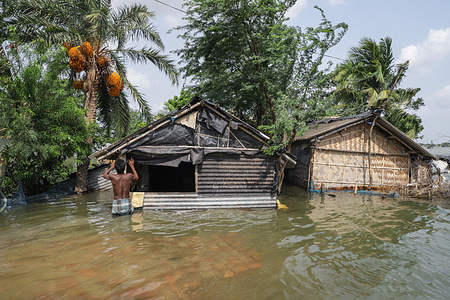 """A man tries to repair his submerged house in a flood-hit coastal village during the aftermath. People of different districts are heavily affected by the super cyclone """"Yaas"""". River embankments have broken and several villages flooded. Salt water has entered the villages and due to that, fishes of pond water are dead. People are facing a lot of difficulties."""