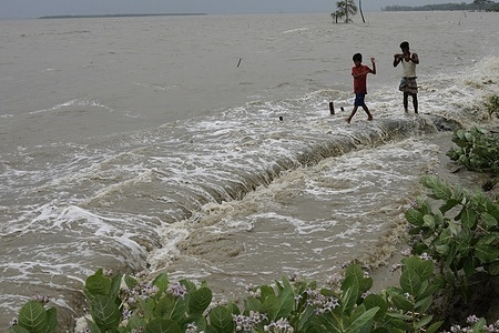 People walk on the embankment after the Cyclone Yaas effect at the coastal area of Patharghata in Barguna. At least two deaths were reported Wednesday as Cyclone Yaas triggered storms and floods in the coastal areas of Bangladesh.