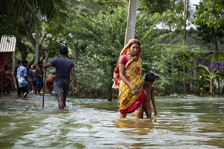 People are seen walking through a flooded road. People of South 24 Parganas and North 24 Parganas are heavily affected as river embankments have broken and several villages flooded after the super cyclone 'Yaas' hitting the coastal areas of West Bengal and Odisha. Salty water from the sea entered inside the villages and as a result, sweet water pond fish died, farm land became incapable of farming anymore, houses submerged in flooded water and many people lost their own belongings.