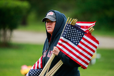 Angie Bowman helps place American flags at Valhalla Memory Gardens for Memorial Day Saturday. Memorial Day, which is Monday, May 31 this year, is a federal holiday for honoring members United States Armed Forces who have died while performing their duties.