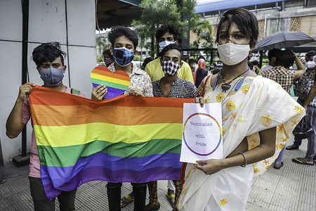 """Transgender people from LGBTQ community hold an LGBTQ Pride flag and """"Vaccinated with Pride"""" printed placard after being vaccinated. 50 Members of LGBTQ community in Kolkata got their first dose of Covishield vaccine from a vaccination centre organized by activists of Techno India and Pranta Katha."""