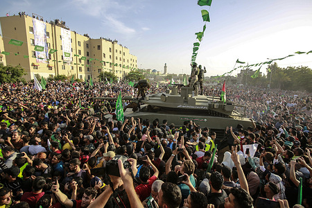 Crowd of Hamas supporters seen around a tank during the rally. Palestinian Hamas staged an anti-Israel rally in the northern Gaza Strip, a parade with weapons in the streets of Gaza city more than a week after a ceasefire between Israel and Hamas.