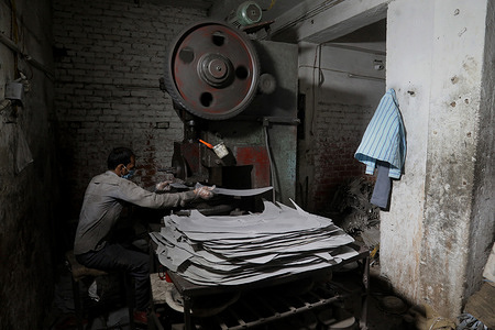 A daily wage worker operates a power pressing circle cutting machine at the utensils manufacturing factory during the ongoing Covid-19 lockdown situation. Delhi extends Covid-19 curfew till June 7, allows construction and manufacturing industries to operate in designated industrial areas.