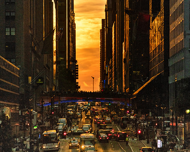 A partially cloud obscured Manhattanhenge sun set. Manhattanhenge is where the rising or setting sun aligns with the street grid in Manhattan, New York City. Here it is as seen from 42nd Street in Manhattan in New York City.