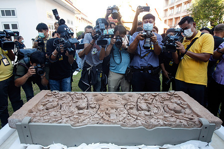 Photographers take photos of one of two sandstone lintels believed to have been stolen from Thailand about 60 years ago. A welcome ceremony was organized to celebrate the return of the two sandstone lintels from the United States to Thailand at the Thailand's National Museum in Bangkok.