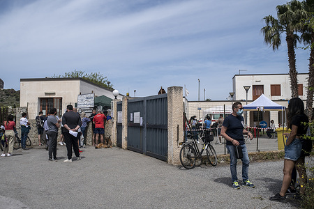 """People seen outside the medical centre in Vulcano. Mass vaccination started in Vulcano island under the guidance of Sicilia Region team, the Special Commissioner for Covid-19 Emergency for Messina Metropolitan Area (Ufficio Commissario Ad Acta per l'Emergenza Covid-19 per l'Area Metropolitana di Messina) and the Red Cross local team. Doses of Moderna and Johnson & Johnson vaccines were administered to residents in order to implement the """"Covid-free islands"""" program for the summer."""