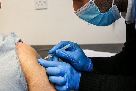 A Covid-19 vaccinator administers the Oxford/AstraZeneca vaccine to a member of public at a vaccination centre in London.