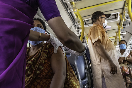 A health worker administers a dose of Covid-19 vaccine in 'Vaccination on wheels' in Kolkata. A bus was turned into a COVID vaccination centre to curb the surge in COVID-19 cases in India.