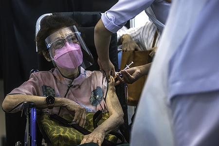 An elderly woman receives a Covid-19 vaccine dose at Malaysia International Trade & Exhibition Centre.The Malaysia government will set up several new mega vaccination centres to boost Covid-19 vaccination capacity and ease overcrowding problem.