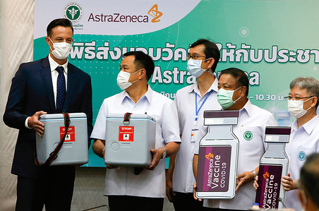 Thailand's Health Minister Anutin Charnvirakul (L2) and senior officials receive the first 1.8 million doses of AstraZeneca's Covid-19 vaccine produced by Siam Bioscience from AstraZeneca's country president (Thailand), James Teague (L) at The Public Health Ministry in Nonthaburi province on the outskirts of Bangkok. AstraZeneca delivered 1.8 million doses of its locally produced Covid-19 vaccine to the Ministry of Public Health on Friday, the first of six million doses scheduled for delivery this month.
