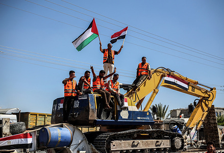 """A Palestinian seen waving flags during the entry of Egyptian equipment for the reconstruction of Gaza. A convoy of bulldozers and heavy equipment provided by Egypt reaches the Palestinian side through the Rafah border crossing between Egypt and Gaza - Egypt sent an aid convoy loaded with excavators, trucks and cranes for the """"reconstruction of Gaza"""", after an Egyptian-brokered ceasefire between Hamas and Israel ended 11 days of violence."""