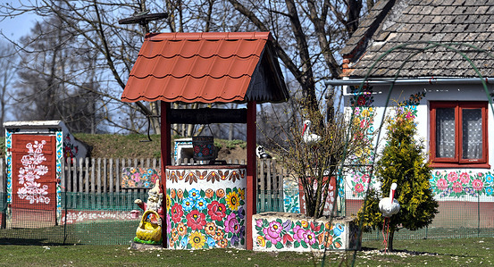 View of a well painted in traditional patterns. The village of Zalipie is known for its custom of hand-painted huts. The characteristic floral patterns can be found on most houses in the village.