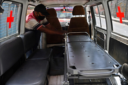 """Mechanics fix  a stretcher bed in a car that is being converted into an ambulance with an oxygen cylinder in Bengaluru. An initiative by """"Drive Without Borders"""" spearheaded by Wasim Memon to help those in need during the second wave of the pandemic is converting 5 Maruthi Omnis into ambulances with oxygen support and 1 into a hearse van. This service is free of charge."""