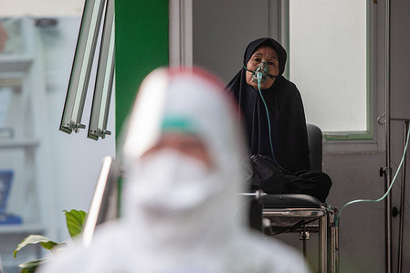 A Covid-19 victim with an oxygen mask is seen behind a health worker ready to be transferred to Wisma Atlet Hospital. Fourteen citizens from Ciracas, a suburban area in East Jakarta are being transported to Wisma Atlet Hospital after getting infected with Coronavirus (COVID-19) disease during their Eid al-Fitr holiday.