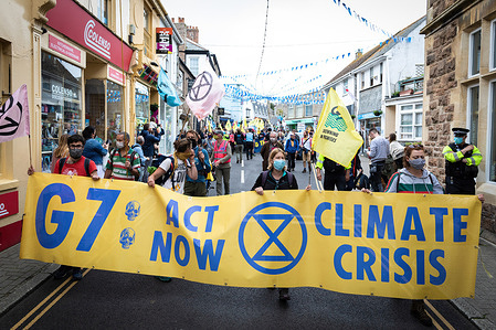 Protesters march with a banner through St Ives village near where delegates are meeting for the 47th G7 during the demonstration.The Extinction Rebellion movement descend onto the small Cornish seaside town. Hundreds of protesters march through the village near where delegates are meeting for the 47th G7. The event sees world leaders come together to discuss matters around climate change.