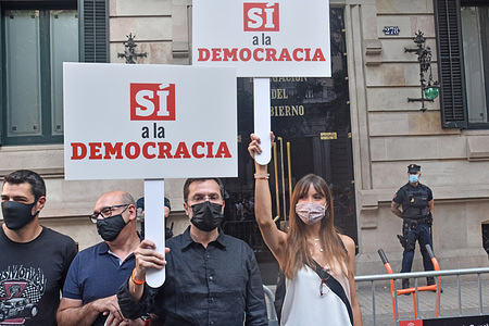 """Protesters hold placards with the slogan """"yes to the democracy"""" during the protest. Hundreds of protesters gathered this afternoon before the Government delegation in Barcelona to protest against the Government's intention to grant pardons to prisoners for the Referendum of October 1, 2017 for the independence of Catalonia. The call, made by the political party of Ciudadanos (Cs),  to which other political parties such as the Popular Party (PP) and social entities such as the Catalan Civil Society (SCC) have joined."""