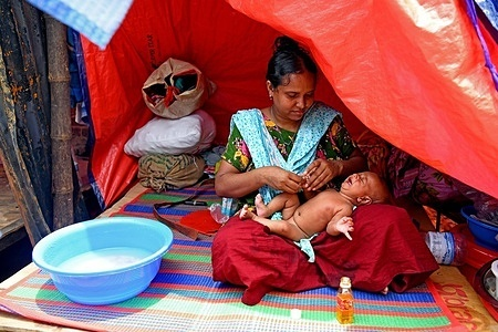 A mother is seen bathing her child in Sat tala slum. According to World Bank, each year up to half a million rural migrants stream into the capital city of Dhaka for work, swelling the rank of the urban poor. Several hundreds of houses were gutted as the devastating fire that broke out at Sat Tala slum at the Mohakhali area in the capital (on 07 June) a few days ago.