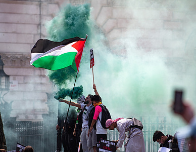 Protesters hold smoke flares and Palestinian flags during a demonstration demanding justice for Palestine.Since May 2021 Israel launched 11-day aerial bombardment to Gaza, killing 248 people, including 66 children and leaving more than 1,900 wounded. In addition, Hamas bombing to Israel during the same period killed 12 civilians including two children. Many pro-Palestinian groups have protested in cities around the world.