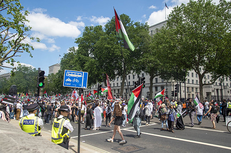 Protesters arrive under the watchful eye of the Police at a Justice for Palestine Protest in Whitehall, London Justice for Palestine protest outside Downing Street in Whitehall timed to coincide with the G7 Summit. The people oppose Israel's latest plans to move Palestinian residents of Jerusalem and it resulted into conflict in the region. The protest was organized by the Palestine Solidarity Campaign UK, CND, Stop the War and Friends of Al Aqsa.