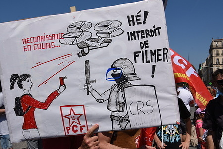 """A protester holding a placard expressing his opinion, during the march. More than 1,500 demonstrators marched in the streets of Marseille for a """"March of Freedom"""" against the far right."""