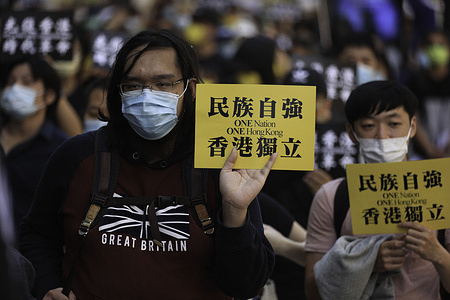 """A pro-democracy activist holding a placard that reads """"one country one Hong Kong"""" during a rally marking the second anniversary of the start of massive pro-democracy protests which roiled Hong Kong in 2019."""