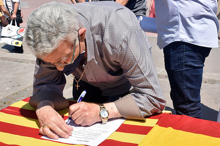 A man leaves his signature against the pardons for the independence prisoners in Spain. The Partido Popular  of Catalonia (PPC) political group has installed a table in the Square of Barcelona to collect signatures of citizens against the pardons that the Government of Spain wants to grant to the independence leaders imprisoned by the Referendum of October 1, 2017.