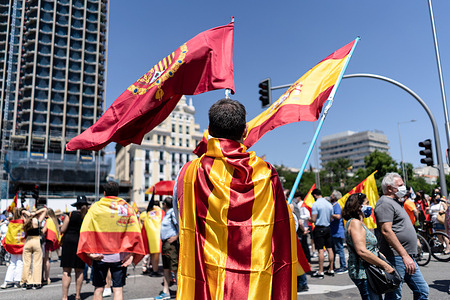 One protester wrapped in a Catalonian flag holds Spanish flags during the protest in Colón Square.Thousands of people in Madrid are protesting the Spanish government's plan to issue pardons to separatist leaders who were convicted for their roles in the independence process of 2017.
