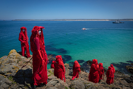 The Red Rebel Brigade which is part of the Extinction Rebellion movement pose on St Ives Head.Environmental Protest Groups gather in Cornwall as the UK Prime Minister, Boris Johnson, hosts leaders from the USA, Japan, Germany, France, Italy and Canada at the G7 Summit in Carbis Bay. This year the UK has invited Australia, India, South Africa and South Korea to attend the Leaders' Summit as guest countries as well as the EU. Protest groups hope to highlight their various causes to the G7 leaders and a global audience as the eyes of the world focus on Cornwall during the summit.