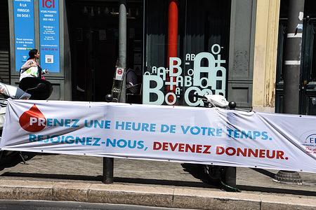 A woman walks past the Maison du Don du Sang, rue de la République with a banner in front of it.Blood donation in Marseille, France.