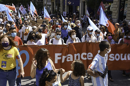"""Protesters hold up a banner and flags during the march in Marseille.More than 1,500 demonstrators marched in the streets of Marseille in a march termed """"March for Freedom"""" against the far right."""