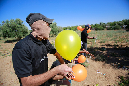 Masked Palestinians launch incendiary balloons from the Gaza Strip towards Israel.Palestinian activists launch incendiary balloons from the Gaza Strip towards Israel in protest to the flag march in East Jerusalem happening now and concerns of a fresh outbreak of violence as some 5,000 right-wing nationalists are due to parade through Jerusalem's Old City waving Israel's blue and white flag. Gaza incendiary balloons burned farmland in at least 13 different locations reportsIsraeli media.