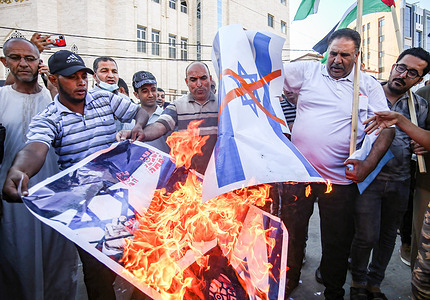 """Protesters burning a portrait of Israeli Prime Minister, Naftali Bennett and the Israeli flag, during a demonstration in the southern Gaza Strip, against the """"flag march"""" organized by far-right Israeli settlers in East Jerusalem."""