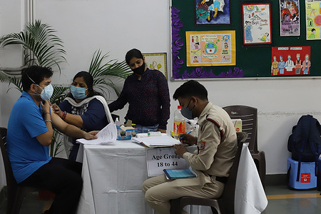 A healthcare worker inoculates a man with a dose of the Covishield vaccine against the Covid-19 coronavirus at a dedicated vaccination centre for international travelers, in Delhi.