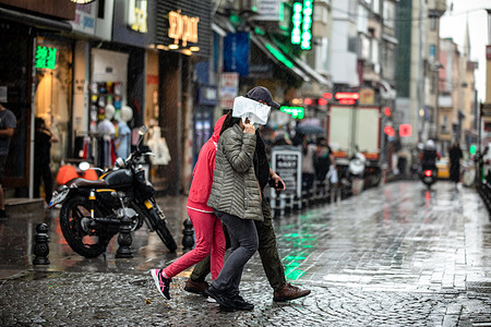 People are seen walking on the street during a rainfall.The rain that started suddenly in Istanbul had a negative impact on life. Citizens had a hard time in and around Kadikoy dock.