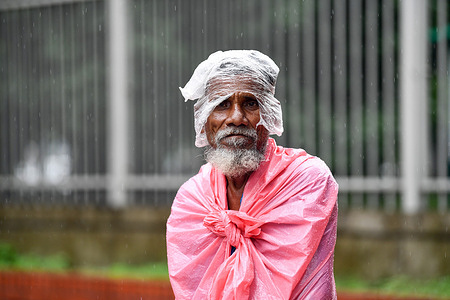 Rickshaw puller Lal Mia standing beside the road waits for passengers during a rainfall in Dhaka.Heavy monsoon downpour caused extreme water logging in most areas of Dhaka city, Bangladesh. Roads were submerged making travel slow and dangerous.