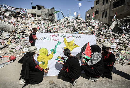 """Children draw on a plaque that reads in Arabic, """"What remains of the olive trees"""" during an exhibition of pictures of the children who lost their lives in the Israeli attacks on Gaza on the ruins of the Sakka family home in Khan Yunis, Gaza destroyed by the Israeli army during the 11 days of violence during the past month"""