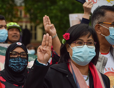 A protester holds up the three-finger salute in Parliament Square during the anti-coup demonstration.  Myanmar protesters marched through central London in opposition to the military coup on Aung San Suu Kyi's birthday.