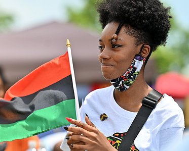 A young black woman holds a Black Liberation Flag during a Juneteenth celebration. President Joe Biden signed into law legislation that would establish June 19 as Juneteenth National Independence Day. Juneteenth is the celebration of the emancipation of blacks. Scranton held a block party for families to celebrate the holiday.
