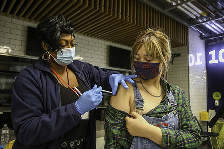 A woman receives her first dose of Pfizer Covid-19 vaccine being offered to adults over the age of 18 at Tottenham Hotspur Stadium as the capital aims for 100,000 doses to be administered on Sunder Sunday.