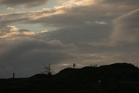 Silhouetted People workout against the backdrop of the rising sun on the top of a hill during the 7th international Yoga day. The World Yoga Day is celebrated annually on June 21, Due to the COVID-19 Second wave of pandemic, there is no annual event.