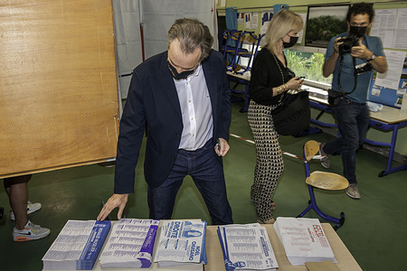 Renaud Muselier (candidate Les Républicains) stands in front of the ballot table at a polling station during the first round of the 2021 regional elections.