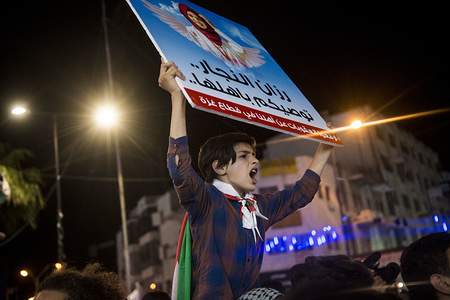 An anti-Abass protester holds a sign depicting Razan Al-Najar a nurse who was killed on during clashes at the Israeli-Gaza border. Palestinians gathered in Al-Manara Square to march in protest of Mahmoud Abass and the Palestinian Authority. A group of pro-Abass supporters briefly scuffled with protesters, however the march remained peaceful after.