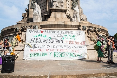 A banner at the Columbus Monument that says, Welcome to Catalonia, squad 421 with closed fists and open hearts, Zapatista tour for life, meeting of peoples united in rebellion and resistance, during the event. Barcelona welcomes the 421 Squadron of the Zapatista Army of National Liberation (EZLN), a libertarian socialist political and militant group of Mexico, on their way through Europe. Composed of different members. The 421 Squad has been received at the Columbus Monument by local collectives and social organizations.
