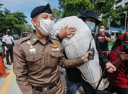 An activist from the Civilian Thailand group carries an effigy of a COVID-19 body as a policeman tries to block him during a protest outside the Public Health Ministry. To demand the government procure alternative Covid-19 vaccines for the public, including children and medical professionals, protesters went to the Public Health Ministry with mock dead bodies to symbolize the Covid-19 victims who have died due to lack of vaccines.