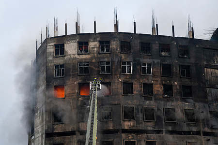 Firefighters try to extinguish a fire inside the building after a fire broke out at a factory named Hashem Foods Ltd in Rupganj of Narayanganj district on the outskirts of Dhaka. At least three people have been killed, 20 others injured and many are feared trapped after a massive fire raged through a factory, the cause of the fire which originated at a ground floor of a multi storey building of the factory is not yet known.